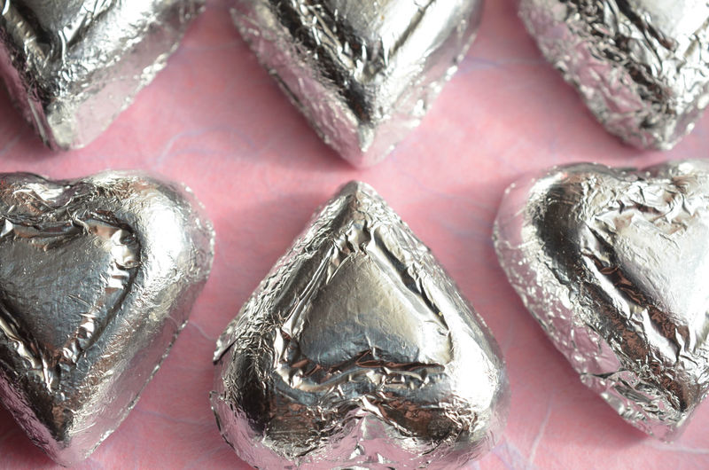 Silver foil wrapped chocolate heart shape candy on pink paper