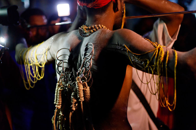 Rear View Of Shirtless Man With Hooks Pierced On His Back At Night