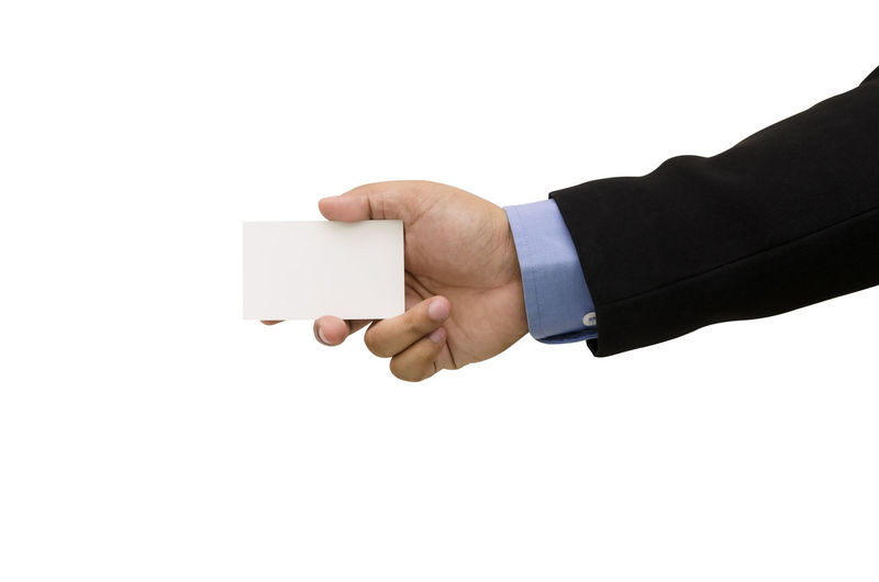 Cropped Hand Of Businessman Holding Card Against White Background