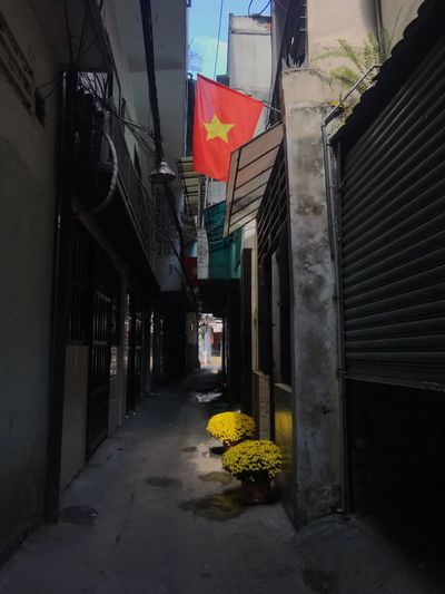 The quite moment on the Lunar holidays Tết Architecture Built Structure Flag Building Building Exterior The Way Forward Direction No People City Day Footpath Alley Patriotism Outdoors Street Residential District Narrow Entrance