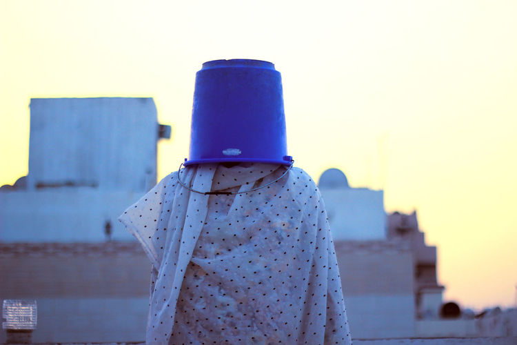 Woman with bucket on head and wrapped in textile standing against sky during sunset