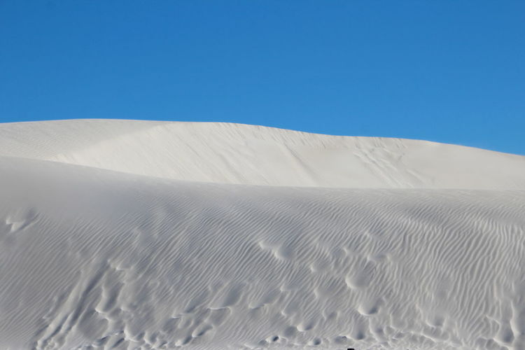 Low Angle View Of Sand Dune Against Clear Blue Sky