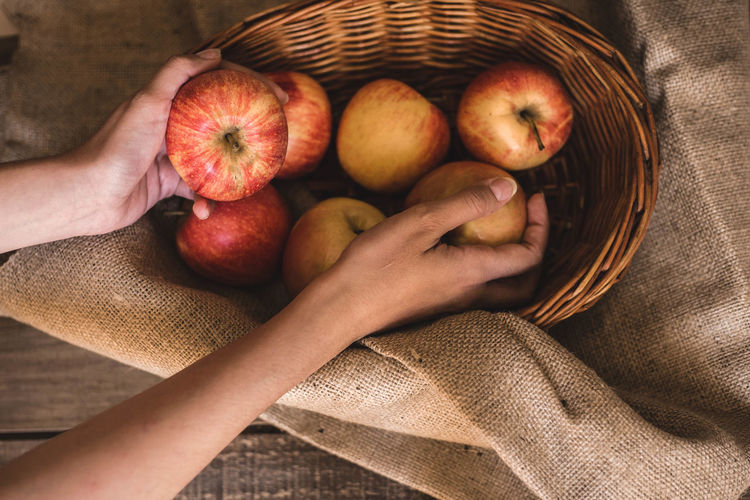 High angle view of hand holding apple in basket
