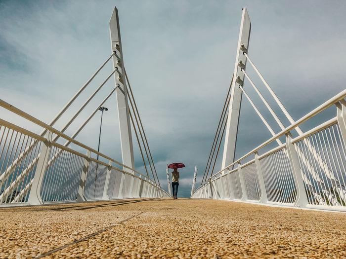 Rear view of woman walking on bridge against cloudy sky