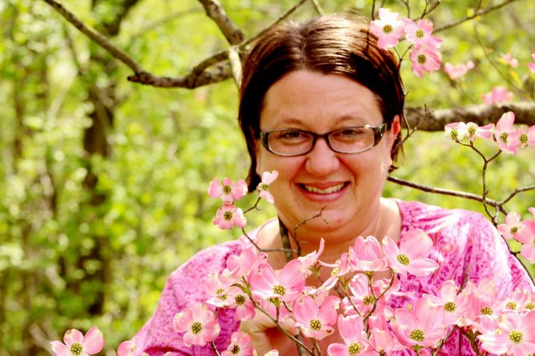 Portrait Of Smiling Woman Standing By Pink Flowers Growing Outdoors