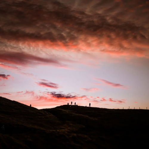 SILHOUETTES OF PEOPLE ON THE TOP OF A HILL