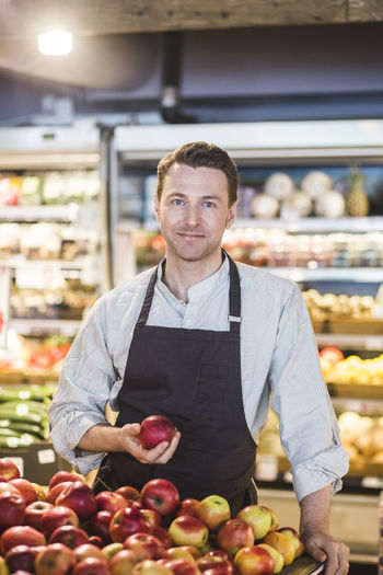 Portrait of smiling man with apples in store