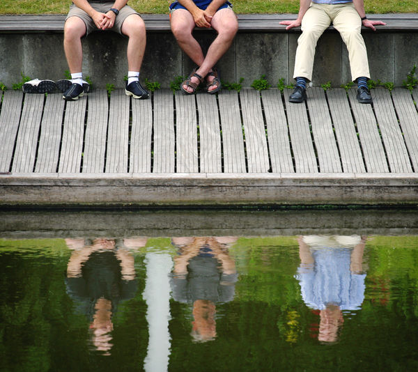 Low section of people sitting on bench by lake