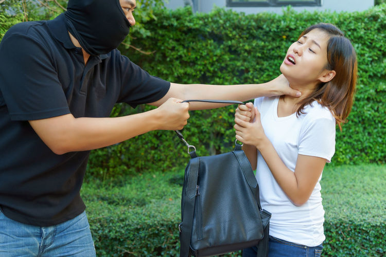 Mugger stealing purse from woman against hedge