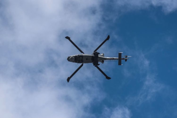 Directly Below Shot Of Helicopter Flying In Blue Sky