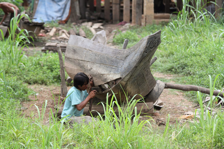 Boat Cambodia Day Focus On Foreground Green Color Man Man Repairing A Boat Outdoors Rural Scene Shipbuilding Stilted Building Wooden Boat