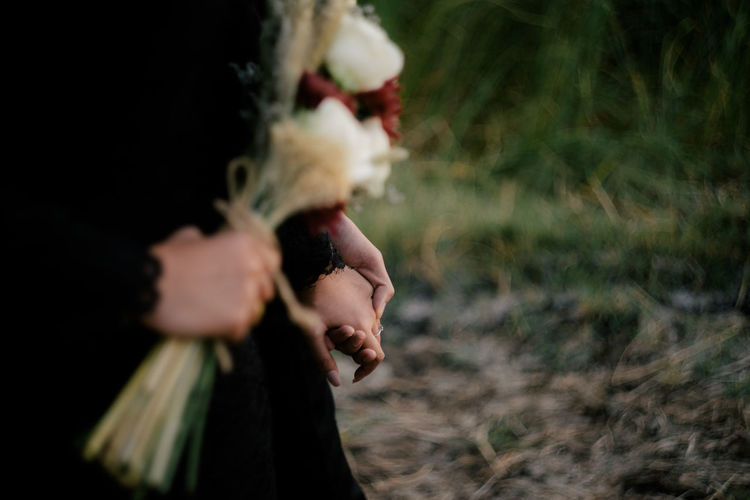 Close-up of woman holding hands on field