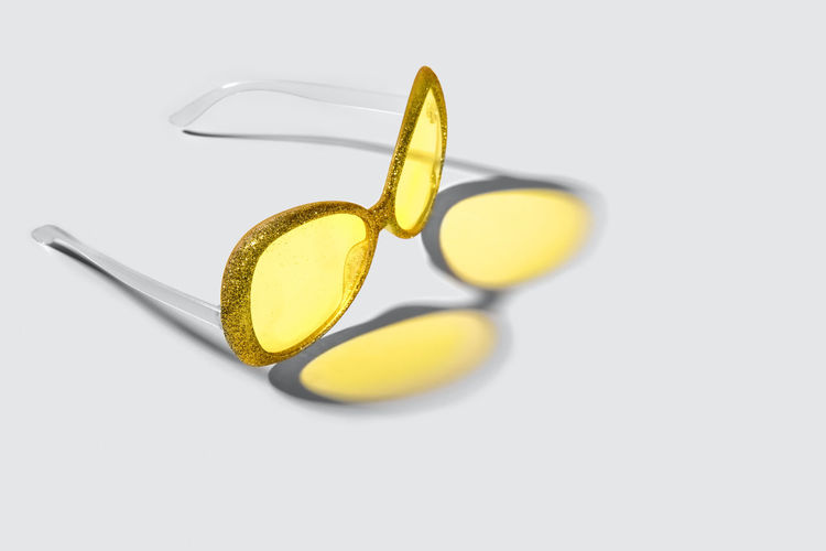 High angle view of eyeglasses on glass against white background