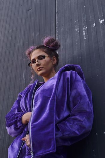 Low angle view of young woman wearing purple jacket by wall