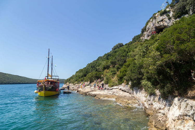 Boat moored in sea by rock formation against clear blue sky