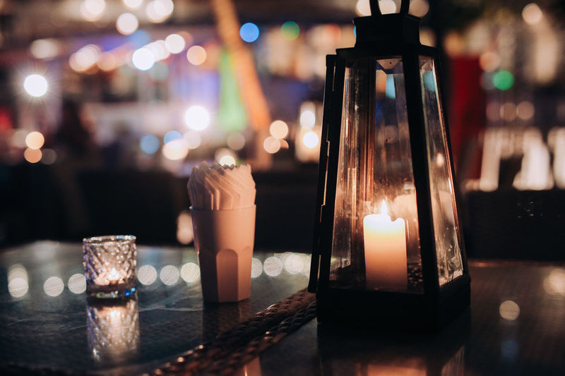 Close-up of tea light candles on table at restaurant
