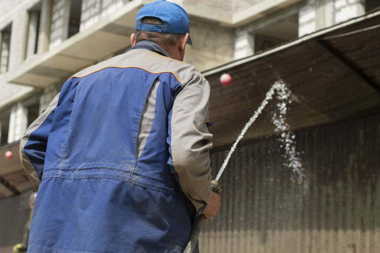 A man washes the fence with a hose. the builder cleans the fence from dirt.