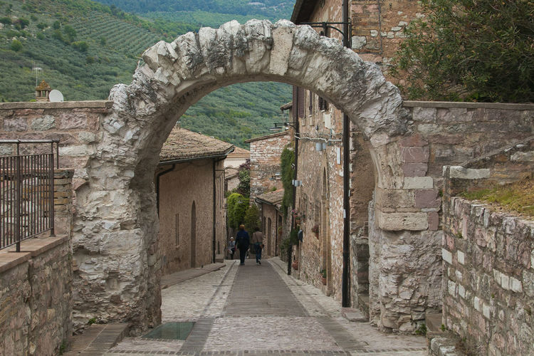Famous roman arch (Porta dei Cappuccini) in Spello. Umbria, Italy Spello Umbria Arch Architecture Alley Narrow Medieval Village Travel Destinations Travel Vacations Holiday Card Wallpaper Italy Europe Historic Historical Building Famous Place Center Built Structure The Way Forward Direction History The Past Day Building Exterior Real People Wall Lifestyles Old Stone Wall Building Adult People Leisure Activity Ancient Walking Walking Around The City