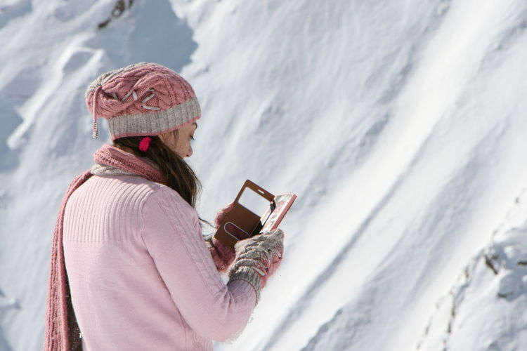 Woman in pink sweater using smart phone against snow covered mountain