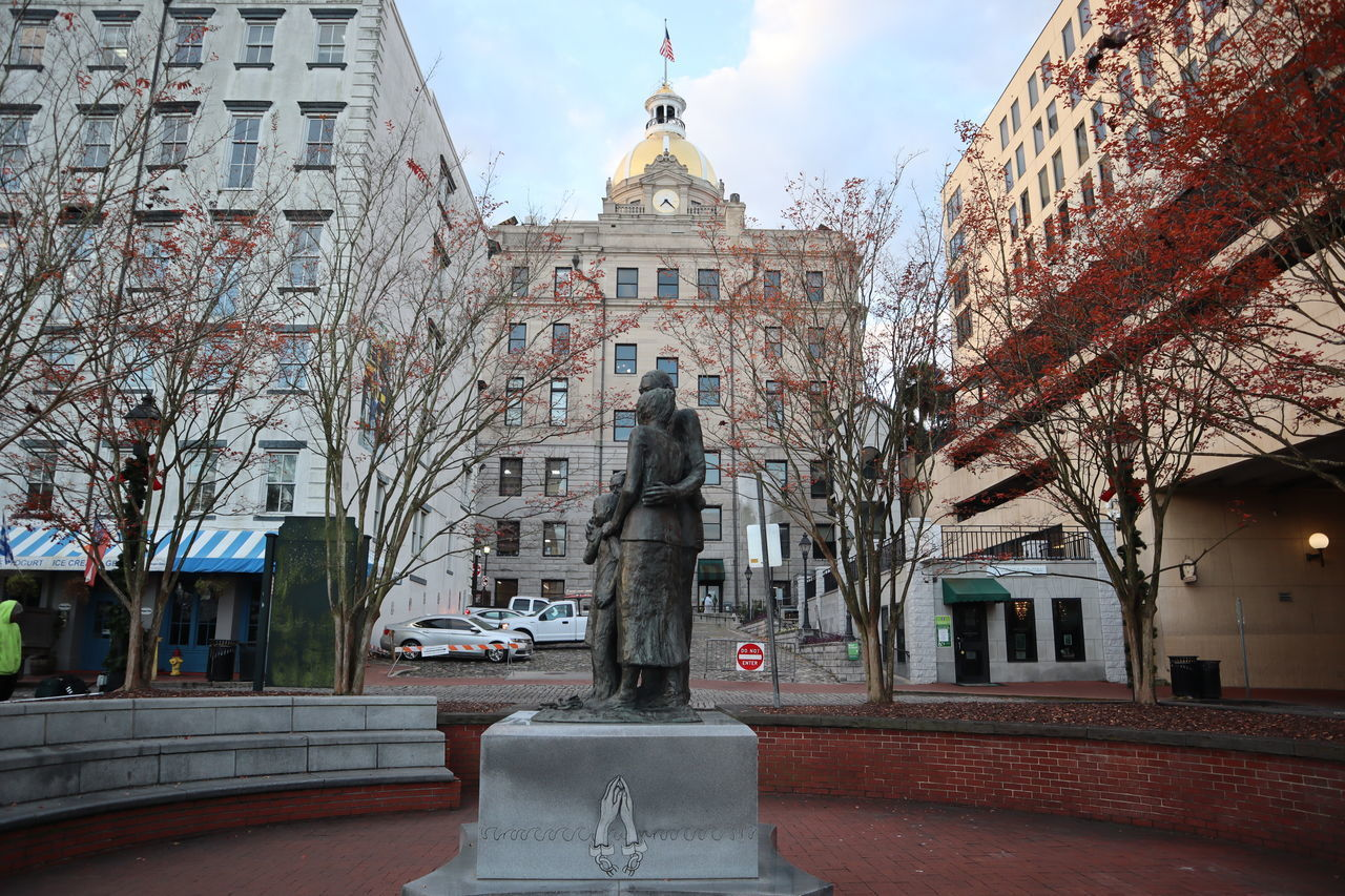 STATUE IN CITY AGAINST BUILDINGS