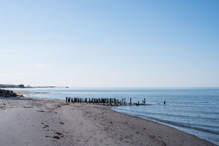 Wooden posts at beach against clear blue sky