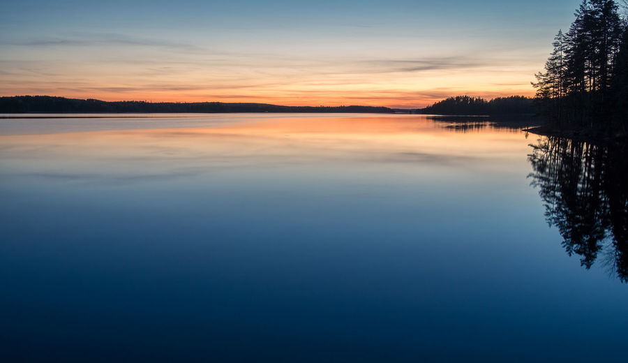 Scenic dawn landscape with lake after sunset at spring evening in Finland Scenics - Nature Tranquility Water Sky Beauty In Nature Tranquil Scene Reflection Lake Waterfront Sunset Idyllic Cloud - Sky Non-urban Scene Standing Water Reflection Lake Silhouette Nature Blue No People Landscape Finland Twilight Blue Moment Dawn Atmospheric Mood