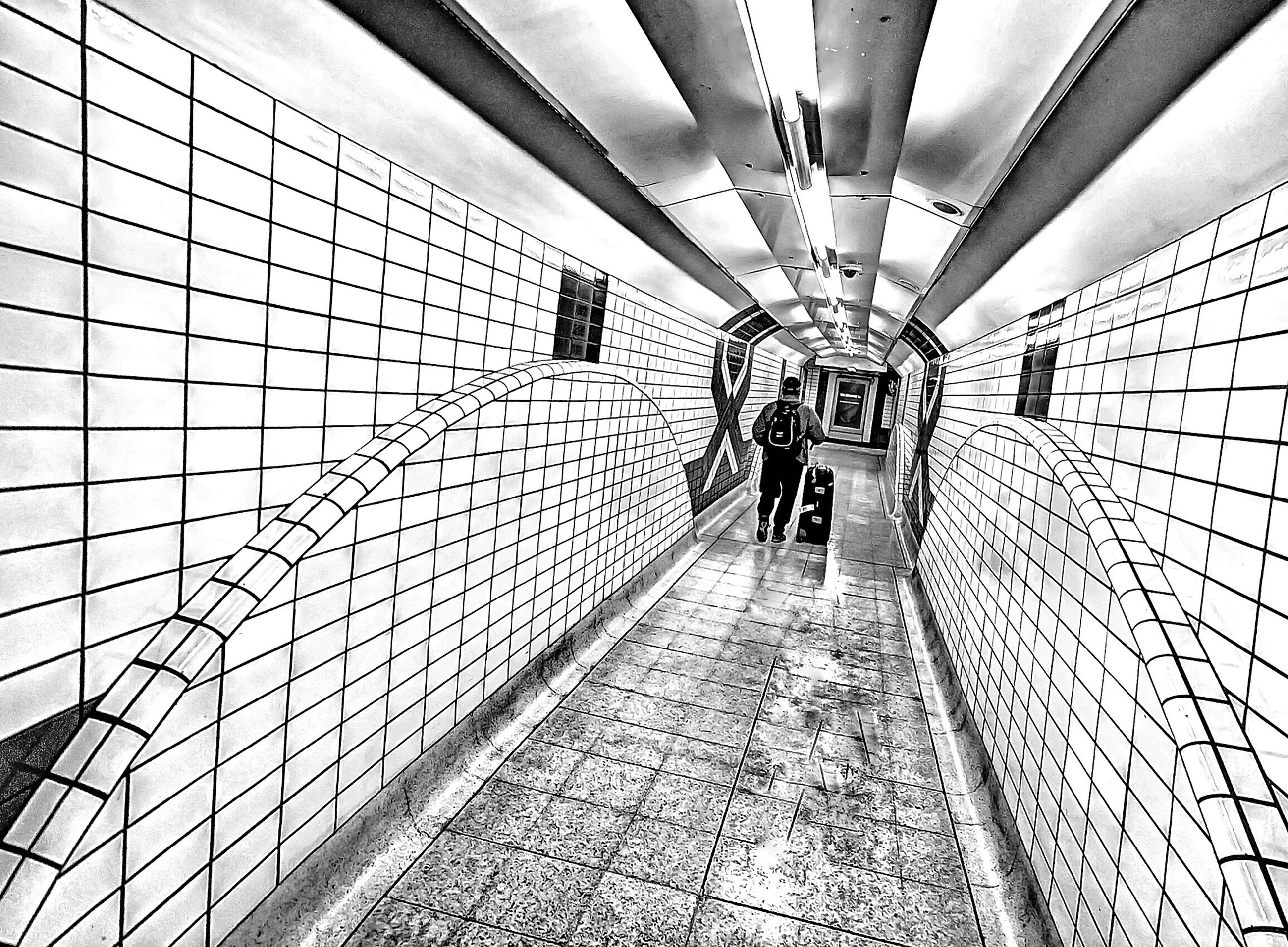 indoors, ceiling, architecture, built structure, the way forward, walking, men, diminishing perspective, lifestyles, modern, tiled floor, transportation, pattern, subway, incidental people, person, flooring, tunnel