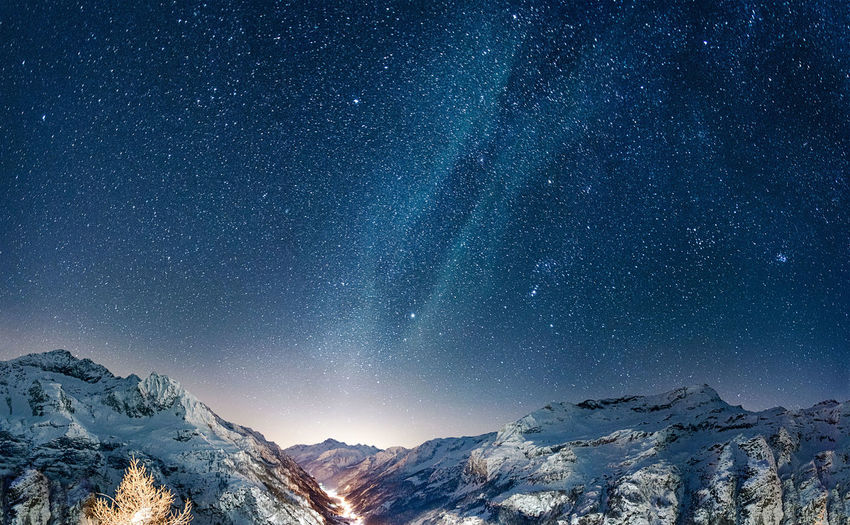 Scenic view of snowcapped mountains against stars at night