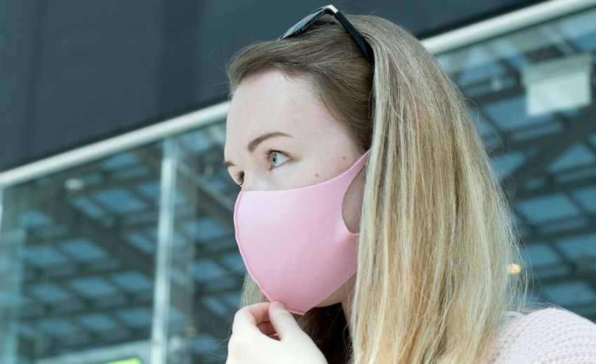 Young woman with blond hair wearing pink reusable mask at the airport or shopping center