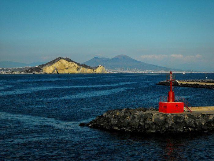 Lighthouse at beach against blue sky