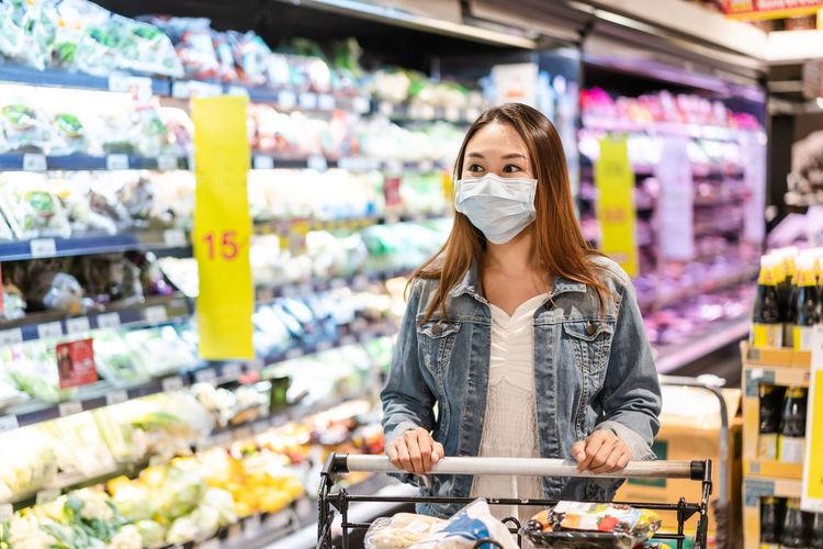 Woman wearing flu mask standing in store