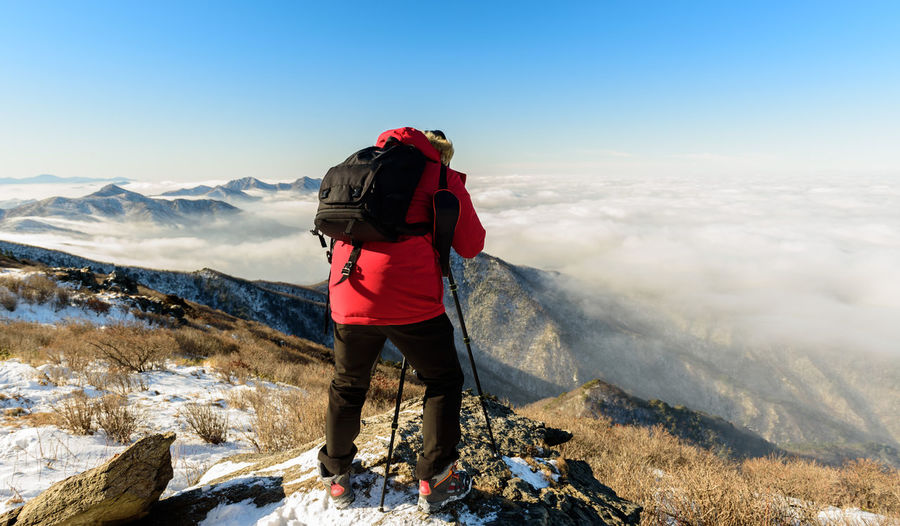 Man Taking Photo Of Snow Covered Mountain Against Sky