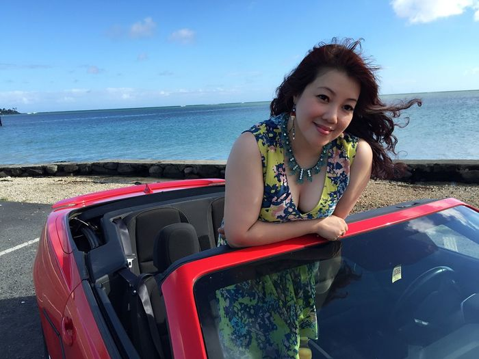Portrait Of Smiling Woman Standing In Convertible Car Against Sea