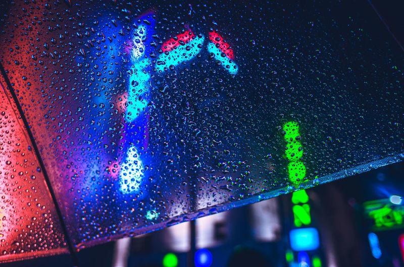Close-Up Of Illuminated Lights Seen Through Wet Umbrella During Rainy Season