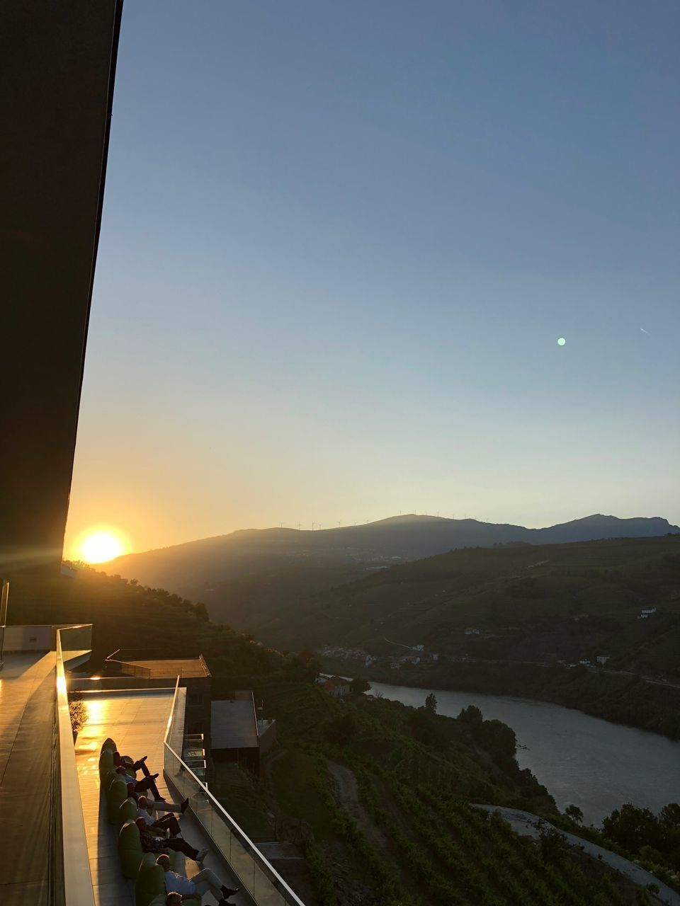 sky, mountain, architecture, scenics - nature, beauty in nature, built structure, sunset, water, building exterior, nature, mountain range, copy space, tranquility, sun, sunlight, building, no people, clear sky, high angle view, outdoors, lens flare