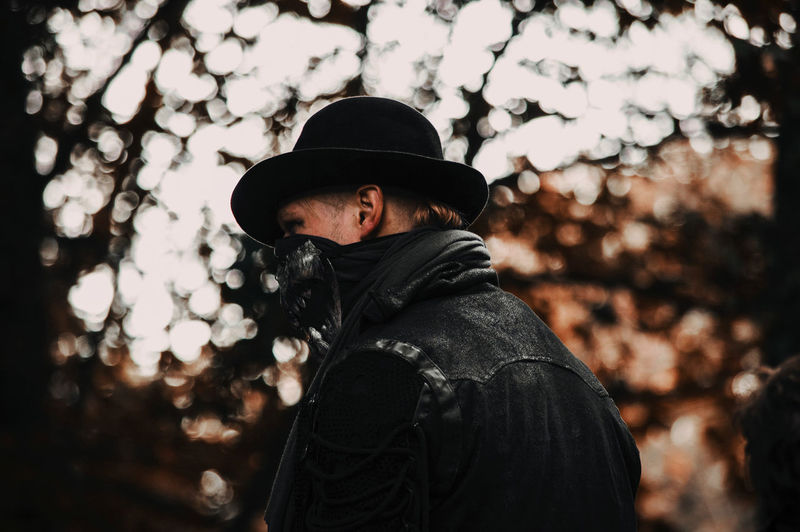 Portrait of man wearing hat standing against trees during winter