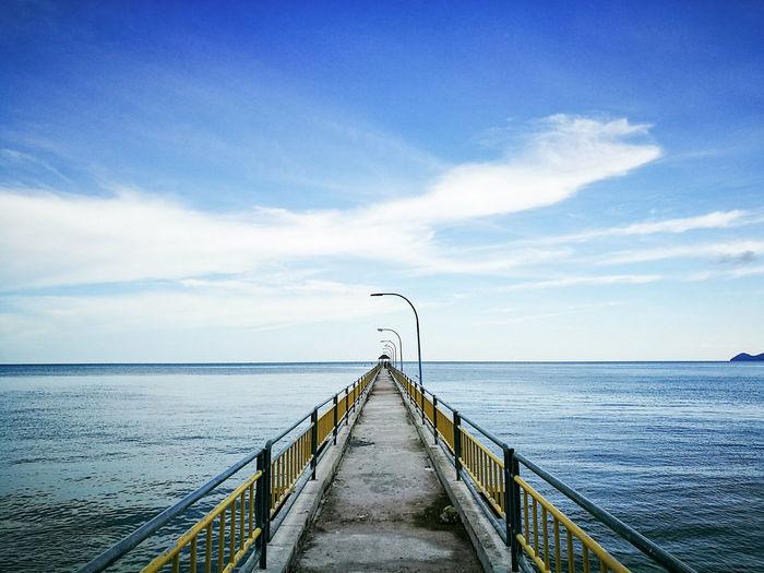 Narrow jetty leading to calm blue sea