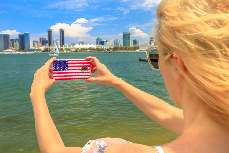 Closeup of tourist takes photo of San Diego By skyline by mobile phone with American flag cover. Blonde woman takes pictures in California summer holidays with her smartphone from Coronado Island, USA San Diego San Diego, California United States America American American Flag Women Mobile Phone Picture Woman Girl Tourist Skyline Beach Cityscape Seascape Water Built Structure Architecture One Person Real People Building Exterior Leisure Activity Nature Lifestyles Holding City Sky Outdoors Skyscraper Office Building Exterior Portrait Headshot Technology Blond Hair Hair Wireless Technology Day Hairstyle