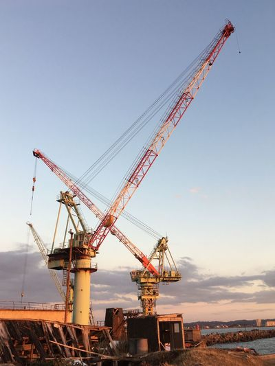 Cranes at construction site against sky