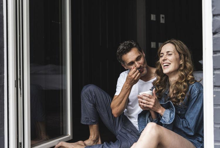 Young couple sitting on window