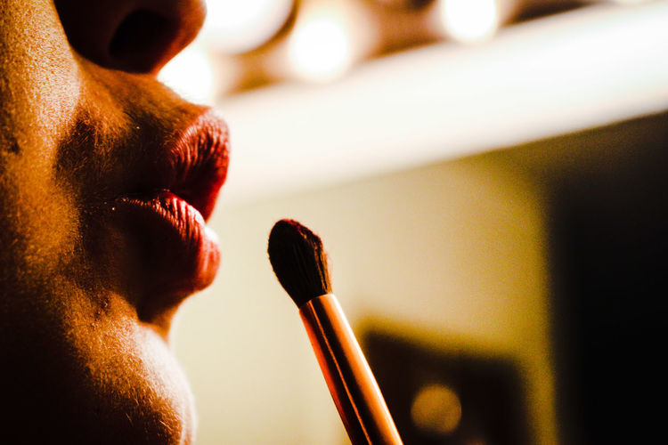 Cropped Image Of Woman Applying Lipstick