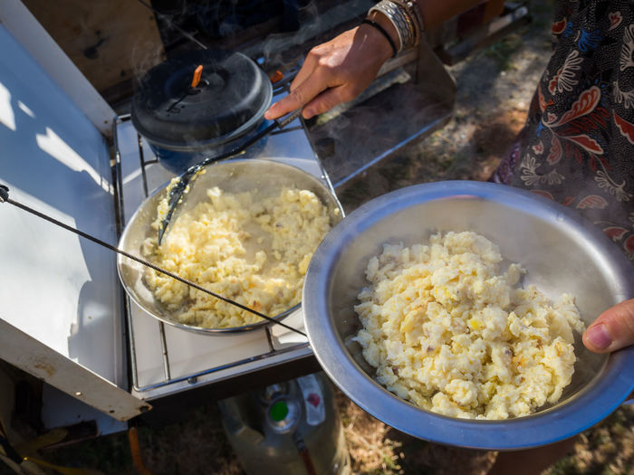 High angle view of scrambled ostrich egg in cooking pan on camping stove