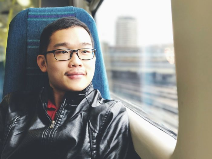 Close-up of young man looking through window while traveling in train