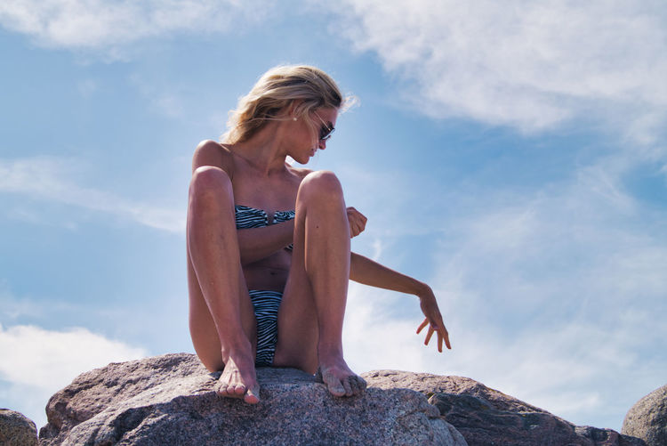 Woman sitting on rock against sky