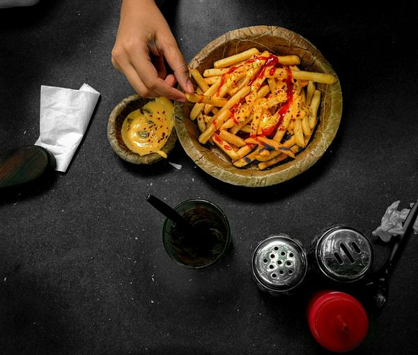 Cropped Image Of Person Holding French Fries Served In Bowl