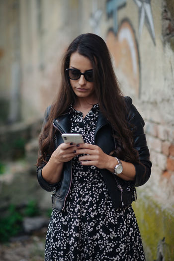 Beautiful young woman using mobile phone outdoors