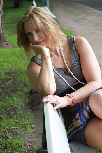 Portrait of smiling senior woman sitting in park