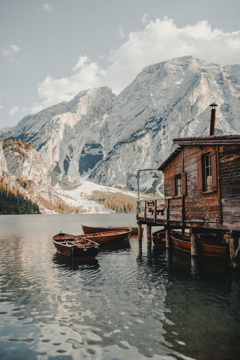 Stilt House With Boats Moored In Lake Against Snowcapped Mountains