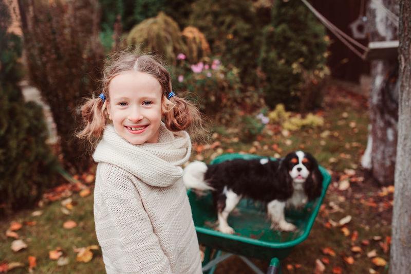 Portrait Of Smiling Girl Standing By Dog In Wheelbarrow On Field