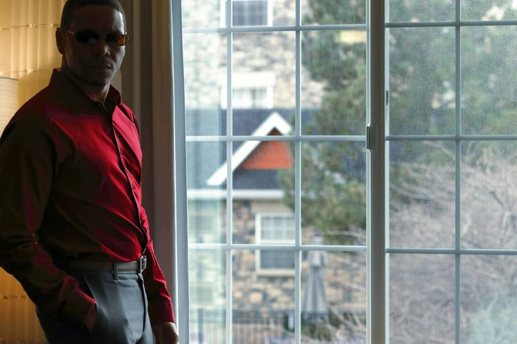 Portrait of man standing by window at home